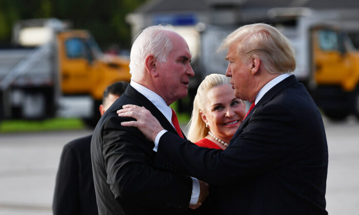 President Donald Trump, right, greets Rep. Mike Kelly (R-Pa.) and his wife Victoria upon arrival at Erie International Airport in Erie, Pa. on Oct. 10, 2018. (Mandel Ngan/AFP via Getty Images)