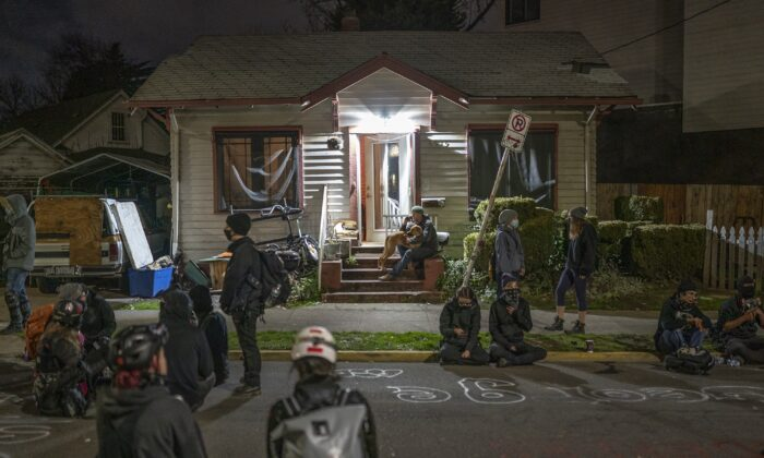 People gather outside a house where a family was set to be evicted, inside a so-called autonomous zone, in Portland, Ore., on Dec. 9, 2020. (Nathan Howard/Getty Images)