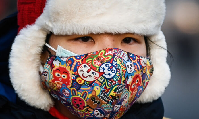 A woman wearing a face mask rides an electric bicycle along a street in Beijing, China on Dec. 10, 2020. (WANG ZHAO/AFP via Getty Images)