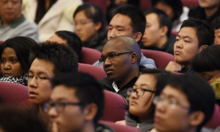 South African and Chinese students listen to a speech by South African President Jacob Zuma at Tsinghua University in Beijing, China on Dec. 5, 2014. (GREG BAKER/AFP via Getty Images)
