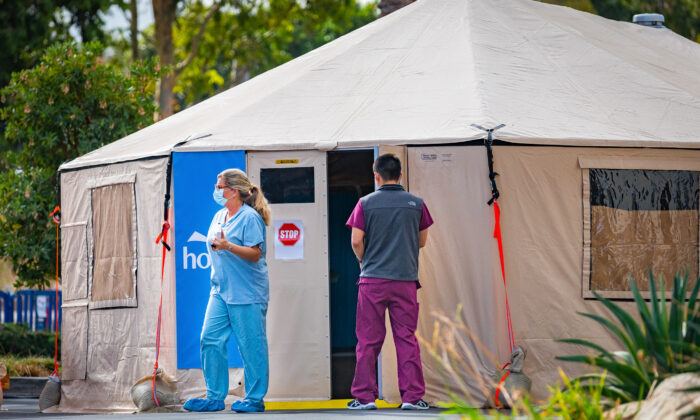 A nurse and a worker stand in front of an emergency tent set up to handle an increase in COVID-19 patients outside of Hoag Memorial Hospital in Irvine, Calif., on Dec. 11, 2020. (John Fredricks/The Epoch Times)