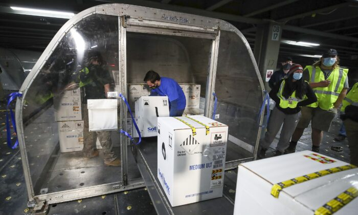 Boxes containing the first shipments of the Pfizer and BioNTech COVID-19 vaccine are unloaded from air shipping containers at UPS Worldport in Louisville, Ky., on Dec. 13, 2020. (Michael Clevenger/Pool/Getty Images)
