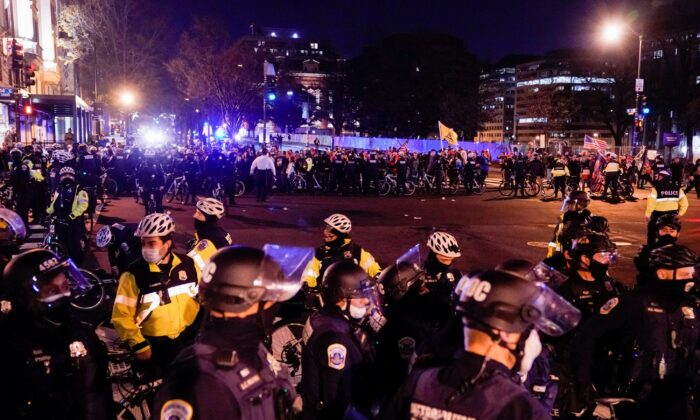 Police officers stand in formation to separate members of the Proud Boys and counter protesters in downtown Washington on Dec. 12, 2020. (Erin Scott/Reuters)