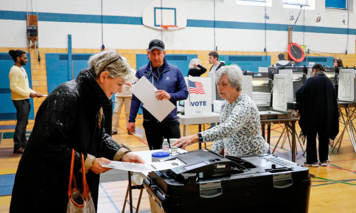 People put their ballots in a tabulation machine in a file photo. (Jeff Kowalsky/AFP via Getty Images)