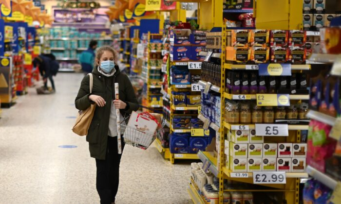 A shopper wearing a protective face covering walks the aisles of a Tesco supermarket in London on Dec. 14, 2020. (Daniel Leal-Olivas/AFP via Getty Images)