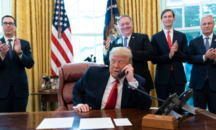 President Donald Trump talks on a phone call with the leaders of Sudan and Israel, as Treasury Secretary Steven Mnuchin (L), Secretary of State Mike Pompeo, White House senior adviser Jared Kushner, and National Security Adviser Robert O'Brien applaud in the Oval Office of the White House on Oct. 23, 2020. (Alex Brandon/AP Photo)