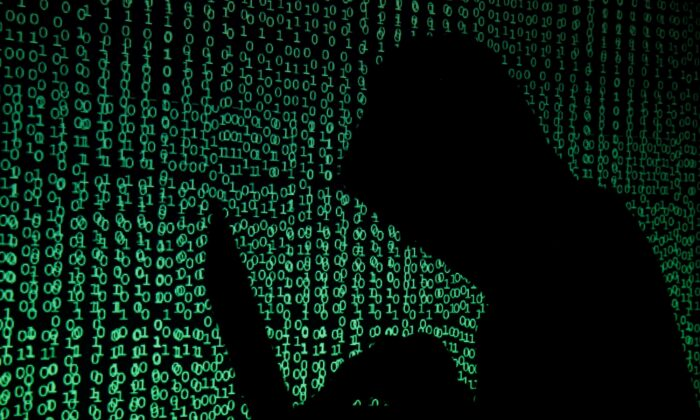A hooded man holds a laptop computer as cyber code is projected on him in this illustration picture taken on May 13, 2017. (Kacper Pempel/Reuters)