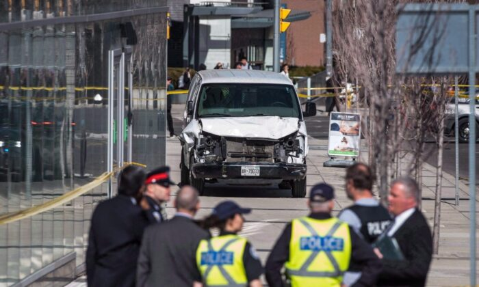 Police are seen near a damaged van in Toronto after a van mounted a sidewalk crashing into a number of pedestrians on April 23, 2018. (The Canadian Press/Aaron Vincent Elkaim)
