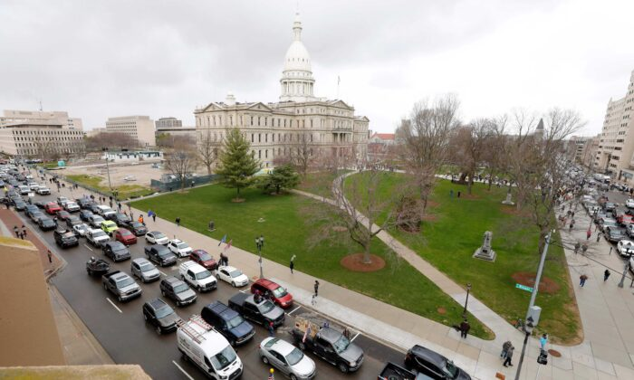 The Michigan State Capitol is seen in the background, as people in vehicles protest lockdown orders, in Lansing, Mich., on April 15, 2020. (Jeff Kowalsky/AFP via Getty Images)