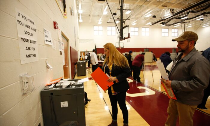 A woman is seen placing her ballot in a tabulation machine after voting in this file photo. (Jeff Kowalsky/AFP via Getty Images)