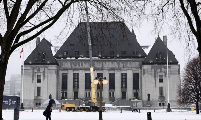 A pedestrian walks past the Supreme Court of Canada in Ottawa on Nov. 26, 2020. (The Canadian Press/Sean Kilpatrick)