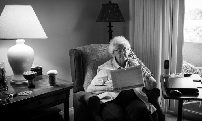 A file photo shows a senior citizen sitting in her room in Freedom Village Retirement Community in Lake Forest, Calif., in 2017. (John Fredricks/The Epoch Times)