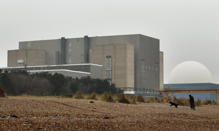 A woman walks her dog on the beach in front of Sizewell nuclear power station in Leiston, England, March 17, 2011. (Oli Scarff/Getty Images)