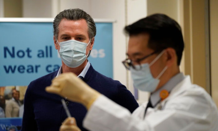 Gov. Gavin Newsom watches as the Pfizer-BioNTech COVID-19 vaccine is prepared by Director of Inpatient Pharmacy David Cheng at Kaiser Permanente Los Angeles Medical Center in Los Angeles, Calif., on Dec. 14, 2020. (Jae C. Hong-Pool/Getty Images)