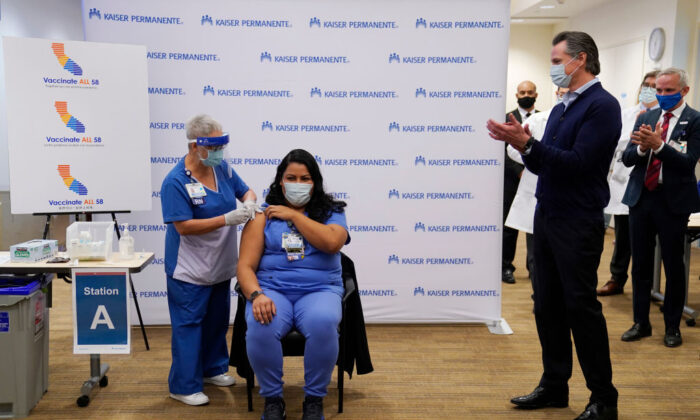 Gov. Gavin Newsom watches as ICU nurse Helen Cordova receives the Pfizer-BioNTech COVID-19 vaccine at Kaiser Permanente Los Angeles Medical Center in Los Angeles on Dec. 14, 2020. (Jae C. Hong-Pool/Getty Images)