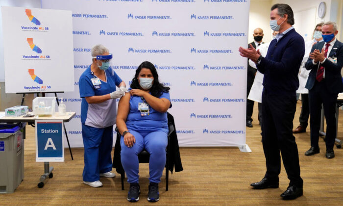 Gov. Gavin Newsom watches as ICU nurse Helen Cordova receives the Pfizer-BioNTech COVID-19 vaccine at Kaiser Permanente Los Angeles Medical Center in Los Angeles, Calif., on Dec. 14, 2020. (Jae C. Hong-Pool/Getty Images)
