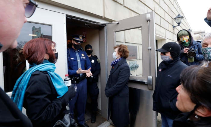 Electors from the GOP are denied entry to the Michigan Capitol as the Electors from the Democratic Party cast their ballot in Lansing, Mich., on Dec. 14, 2020. (Jeff Kowalsky/AFP via Getty Images)