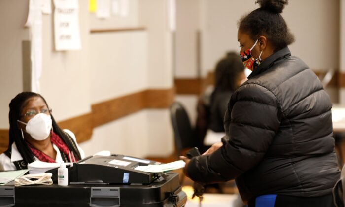 A voter puts their ballot in the tabulation machine after voting in the 2020 general election at the Northwest Activities Center in Detroit, Mich., on Nov. 3, 2020. (Jeff Kowalsky/AFP via Getty Images)