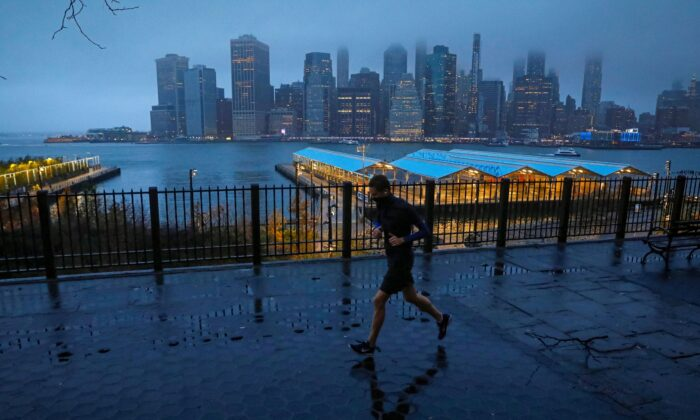 A man runs along the Brooklyn Heights Promenade as fog covers lower Manhattan in New York on Nov. 30, 2020. (Brendan McDermid/Reuters)