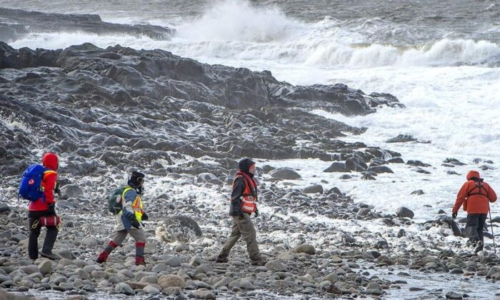Members of a ground search and rescue team walk along the shore of the Bay of Fundy in Hillsburn, N.S. in an area where empty life-rafts from a scallop fishing vessel where reported on Dec. 15, 2020. (The Canadian Press/Andrew Vaughan)