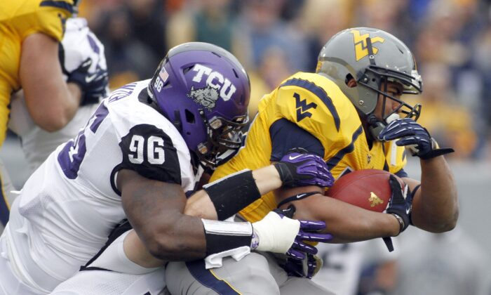 Shawne Alston #20 of the West Virginia Mountaineers is tackled by Chucky Hunter #96 of the TCU Horned Frogs during the game at Mountaineer Field in Morgantown, West Virginia on Nov. 3, 2012.  (Justin K. Aller/Getty Images)