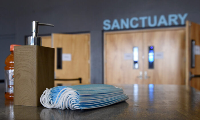 Hand sanitizer and surgical masks are placed on tables for those that want to use them at the sanctuary entrance of the International Church of Las Vegas in Las Vegas, Nevada, on May 31, 2020. (Ethan Miller/Getty Images)