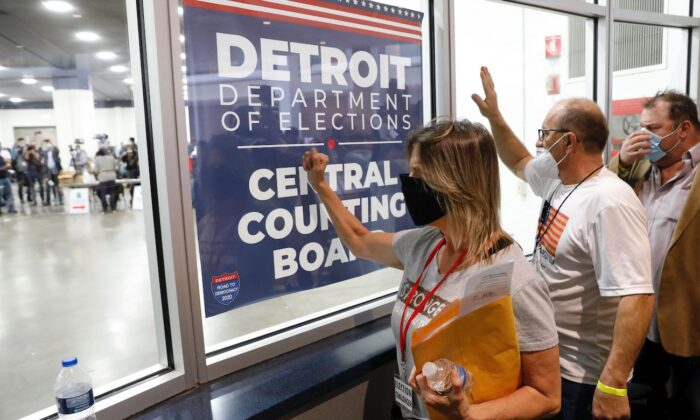People stand outside the room where absentee ballots for the 2020 general election are being counted at TCF Center in Detroit, Michigan, on Nov. 4, 2020. (Jeff Kowalsky/AFP via Getty Images)