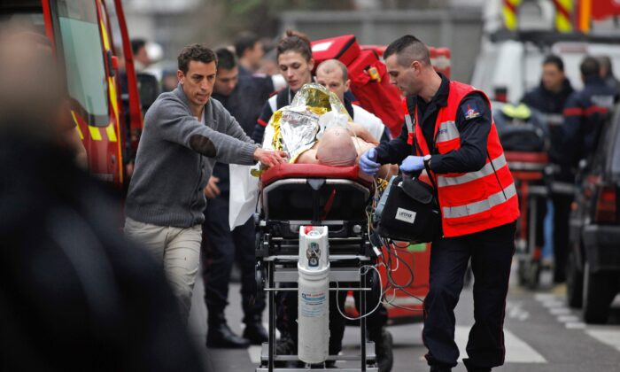 An injured person is transported to an ambulance after a shooting at the French satirical newspaper Charlie Hebdo's office in Paris, on Jan. 7, 2015. (Thibault Camus/AP Photo)
