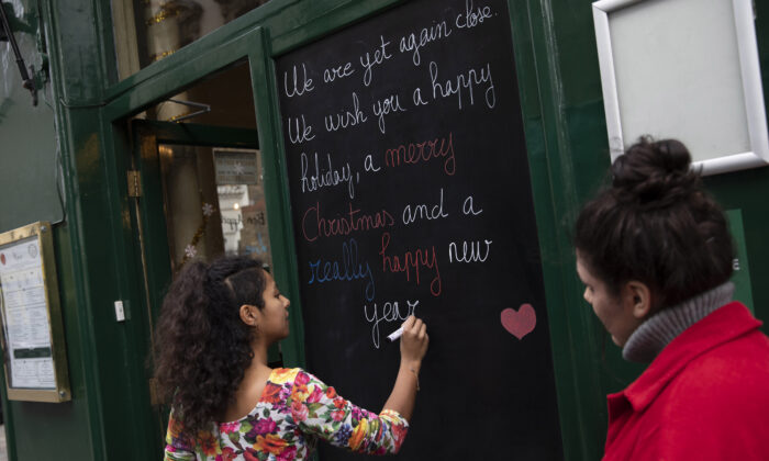 A restaurant worker at Le Garrick in Covent Garden writes a sign to customers in London on Dec. 16, 2020. (Dan Kitwood/Getty Images)