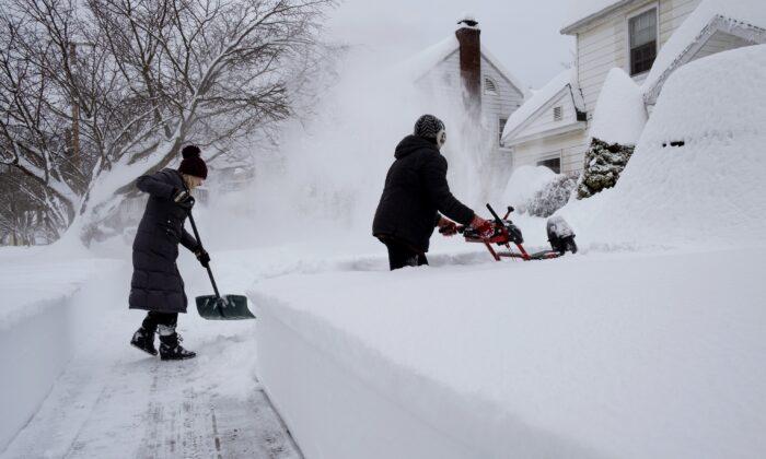 Susan Iannuzzi, left, and Linda Marzell clear a sidewalk after a heavy snowfall on street in Binghamton, N.Y., on Dec. 17, 2020. (Craig Ruttle/AP Photo)