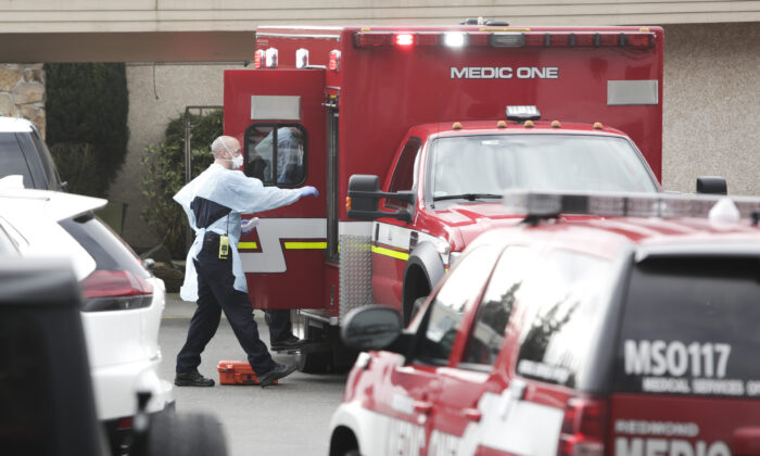 Ambulance staff prepare to transport a patient from the Life Care Center nursing home where some patients died from COVID-19, in Kirkland, Wash., on March 5, 2020. (Jason Redmond/AFP via Getty Images)