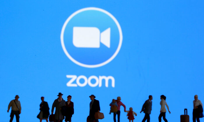 Small toy figures are displayed in front of a Zoom logo in this illustration taken on March 19, 2020. (Reuters/Dado Ruvic/Illustration)