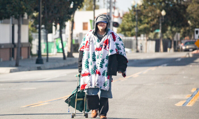 A homeless man walks in the middle of the road in Santa Ana, Calif., on Dec. 17, 2020. (John Fredricks/The Epoch Times)