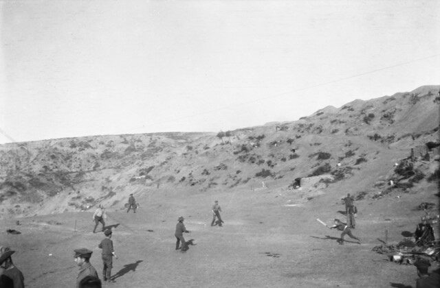 A game of cricket was played on Shell Green in an attempt to distract the Turks from the imminent departure of allied troops. Major George Macarthur Onslow of the Light Horse in batting, is being caught out. Shells were passing overhead all the time the game was in progress. (Australian War Memorial)