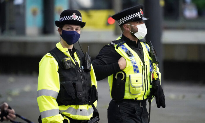 Police officers wear face masks as they patrol the city centre in Manchester, England, on Oct. 20, 2020. (Christopher Furlong/Getty Images)