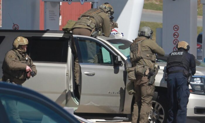 RCMP officers prepare to take a person into custody at a gas station in Enfield, N.S. on April 19, 2020. (The Canadian Press/Tim Krochak)