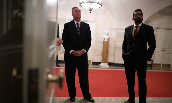 Kash Patel, left, then-National Security Council director of counterterrorism, stands with Sen. Lindsey Graham (R-S.C.) in the White House in Washington on Oct. 29, 2019. (Alex Wong/Getty Images)