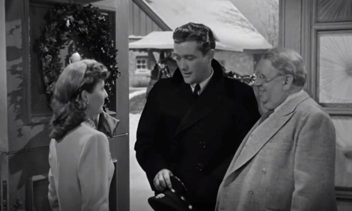"(L–R) Elizabeth Lane (Barbara Stanwyck) greets Jefferson Jones (Dennis Morgan) while her uncle Felix (S.Z. Sakall) watches in ""Christmas in Connecticut."" (Warner Bros.)"