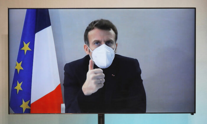 French President Emmanuel Macron is seen on a screen as he attends by video conference a round table for the National Humanitarian Conference, taken at the Foreign Ministry in Paris on Dec. 17, 2020. (Charles Platiau/Pool via AP)