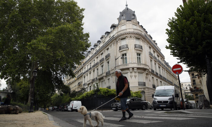 A man walks his dog next to an apartment building owned by Jeffrey Epstein in Paris on Aug.13, 2019. (Francois Mori/AP Photo)