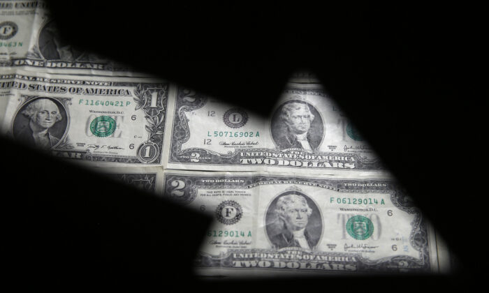 U.S. dollar banknotes are seen through a printed stock graph in this illustration taken on Feb. 7, 2018. (Dado Ruvic/Reuters)