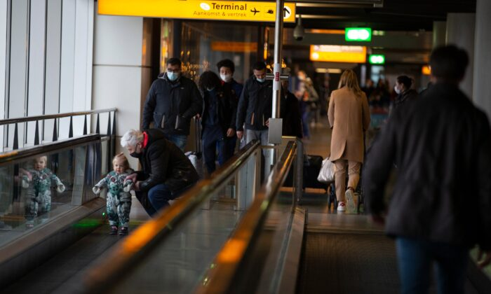 Arriving and departing passengers use the flat escalators at Schiphol Airport, near Amsterdam, Netherlands, on Dec. 18, 2020. (Peter Dejong/AP Photo)
