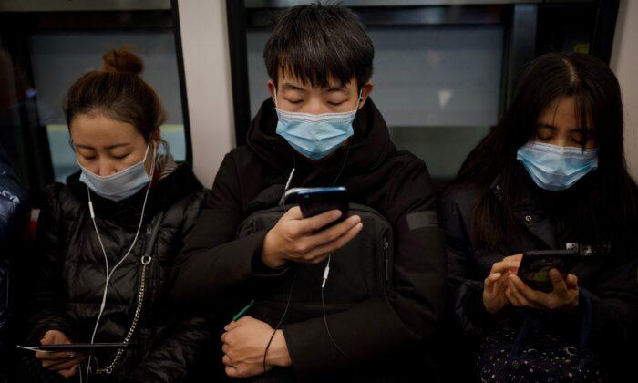 People wearing face masks use their mobile phones on a subway in Beijing on Dec. 19, 2020. (NOEL CELIS/AFP via Getty Images)
