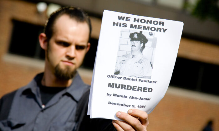 A counter-protester holds a handbill in remembrance of slain police officer Daniel Faulkner at a rally for Faulker's convicted murderer, death-row inmate Mumia Abu-Jamal outside the Federal Court building in Philadelphia, on May 17, 2007. (Jeff Fusco/Getty Images)