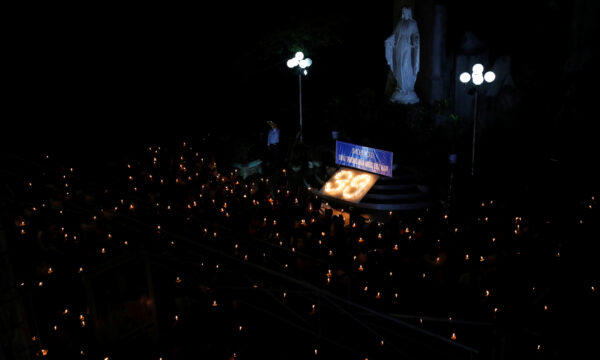 Catholic believers hold lit candles during a mass prayer for 39 Vietnamese