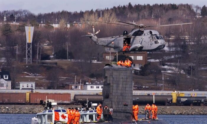 A Sea King helicopter flies over HMCS Corner Brook, the third of four Victoria-class submarines leased from Britain, as it arrives in Halifax on March 10, 2003. (The Canadian Press/Andrew Vaughan)