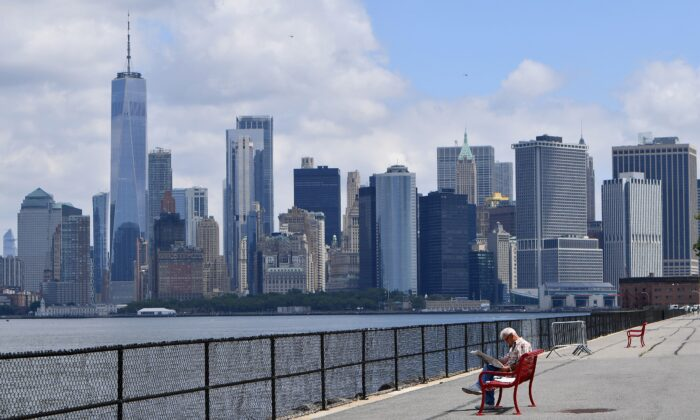 A man visits New York City's Governors Island, with the Manhattan skyline visible in the distance, on July 15, 2020. (Angela Weiss/AFP via Getty Images)