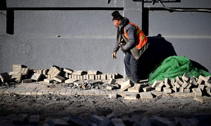 A worker lays bricks along a street in Beijing, China on Dec. 4, 2020. (NOEL CELIS/AFP via Getty Images)