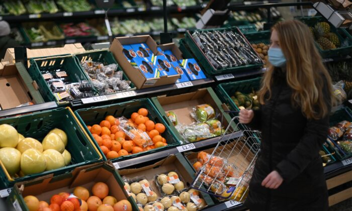 A shopper wearing a protective face covering browses for fruit and vegetables in a Tesco supermarket in London, on Dec. 14, 2020. (Daniel Leal-Olivas/AFP via Getty Images)