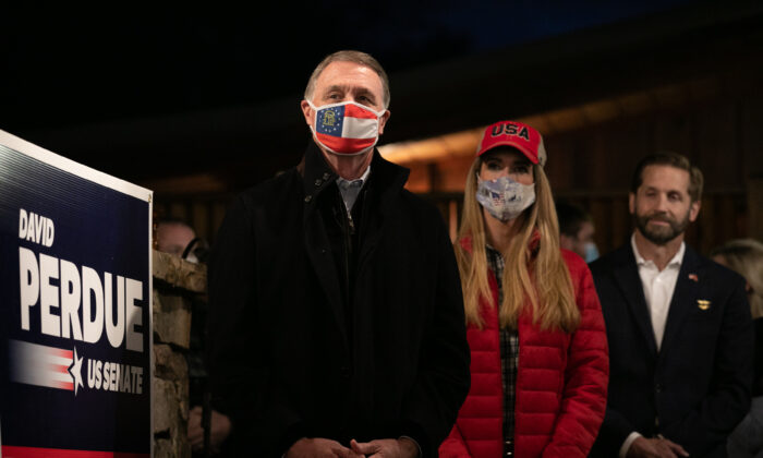 Sens. David Perdue (R-Ga.), left, and Kelly Loeffler (R-Ga.) stand during a rally in Cumming, Ga., on Dec. 20, 2020. (Jessica McGowan/Getty Images)